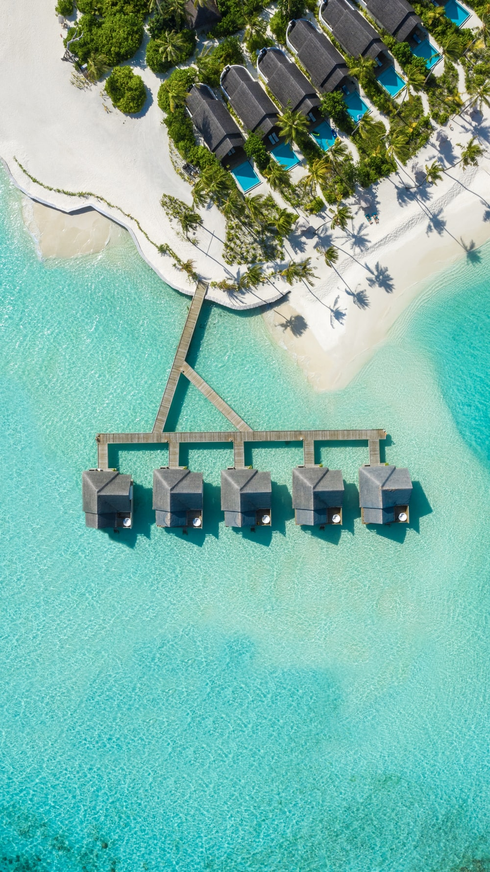 brown huts on body of water in aerial photography