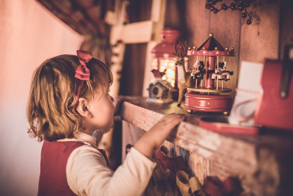 girl standing in front of carousel toy