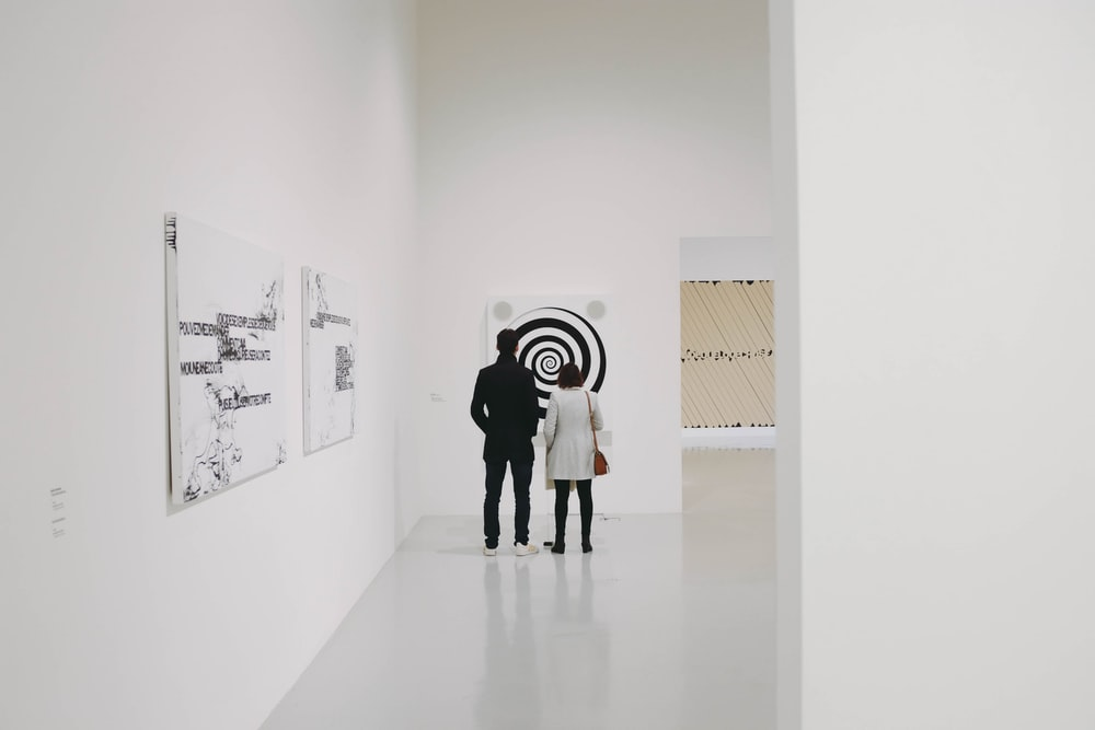 man and woman looking at white and black spiral painting