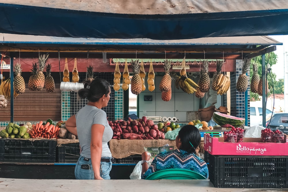 two women facing fruits and vegetable stall