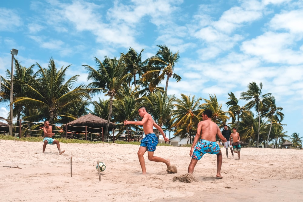 several men playing football on beach sand