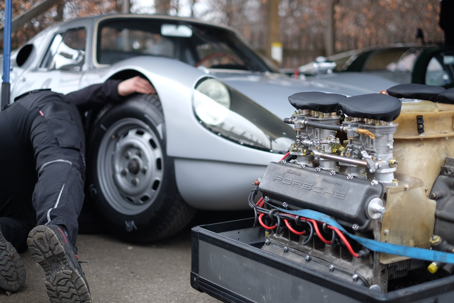 Man doing tune-up on a silver car