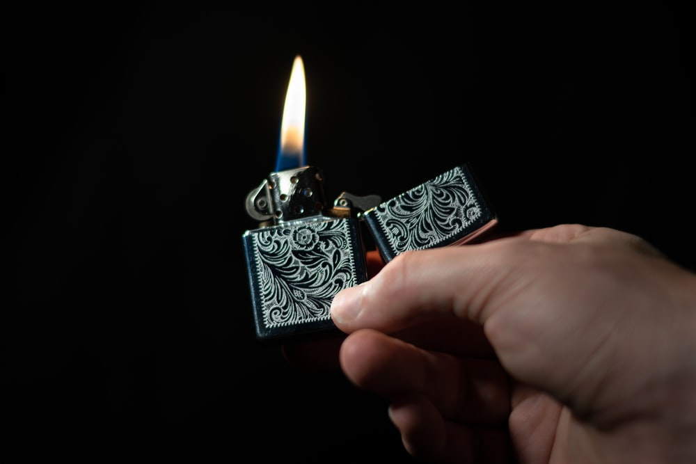 person holding silver and black flip lighter