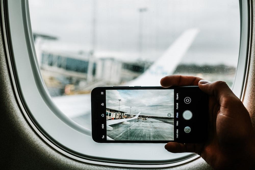 black iPhone capturing plane wing