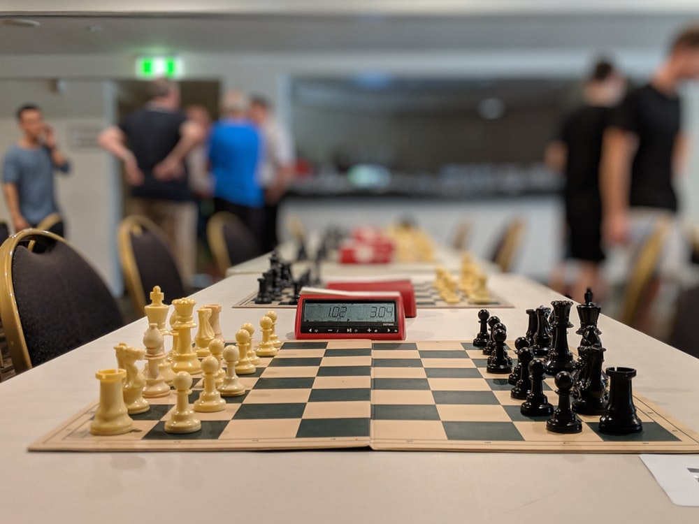 black and white chess board near people standing inside building
