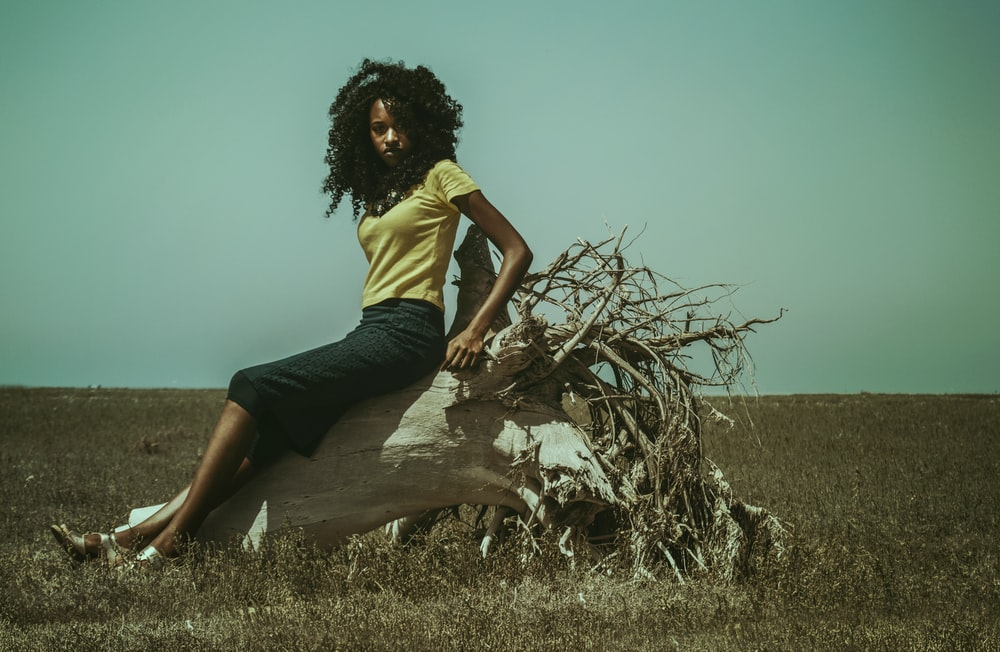 woman sitting on top of driftwood on field at daytime