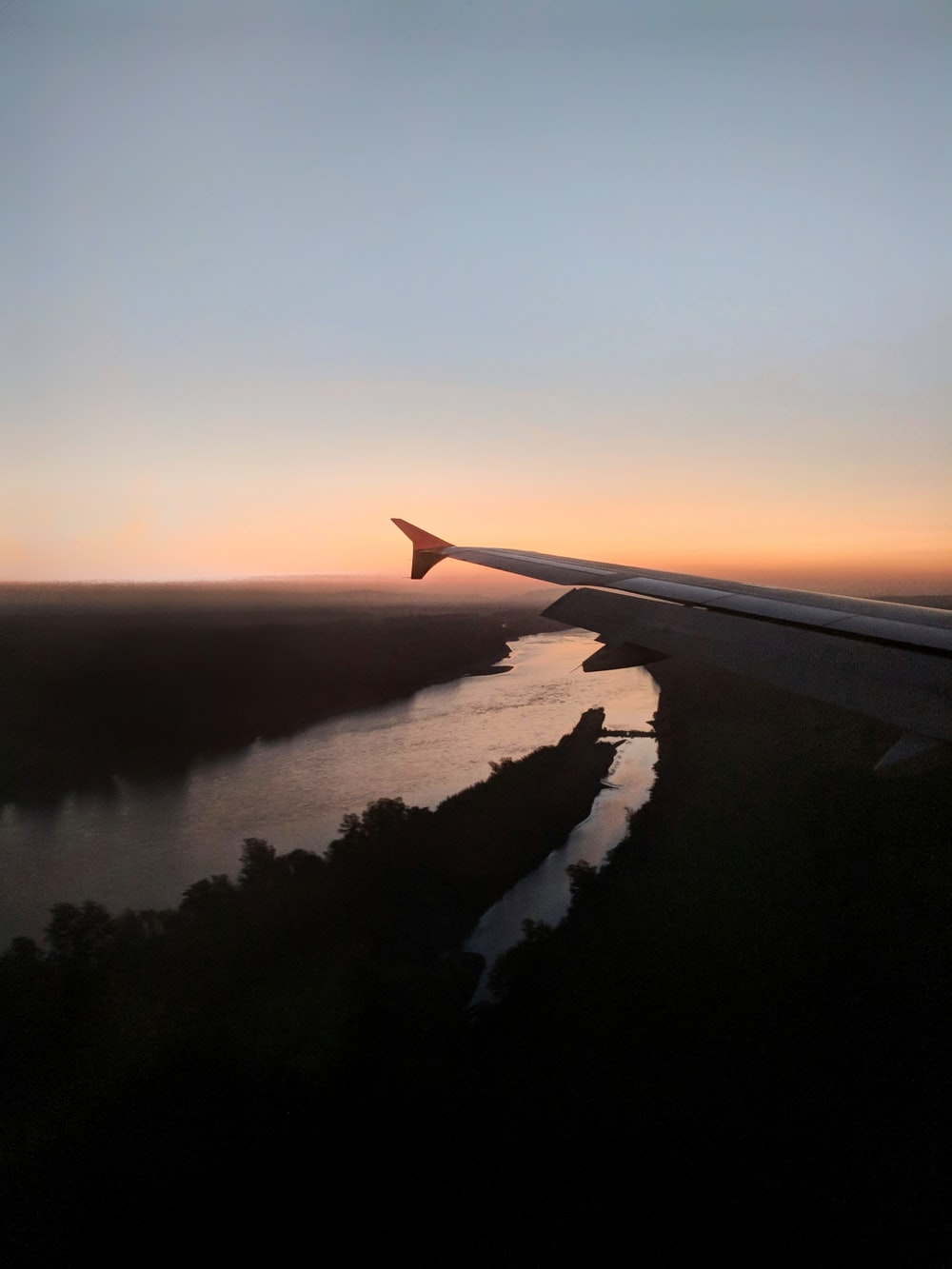 aircraft wingtip overlooking river at night time