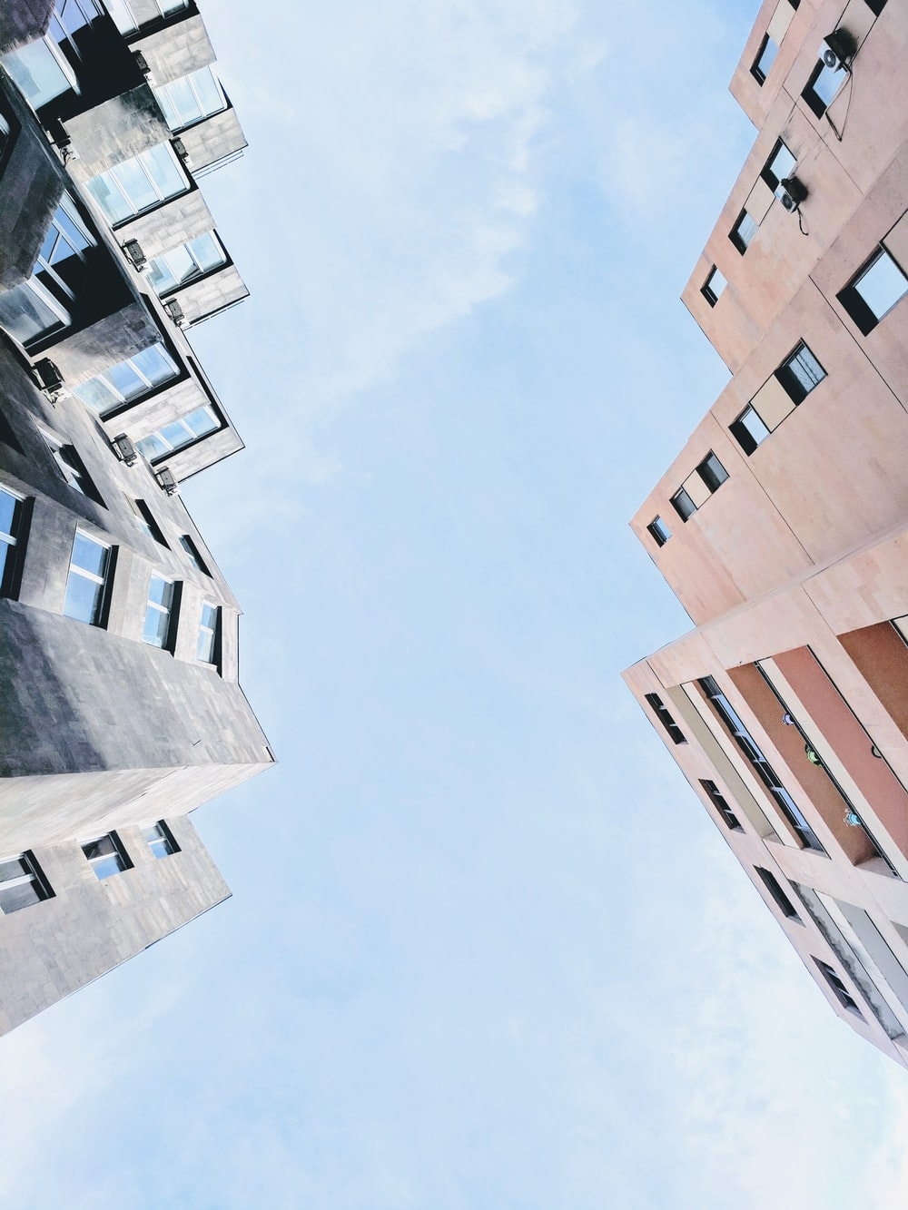 low angle photography of highrise building under cumulus clouds