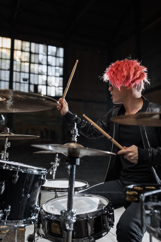 man wearing black jacket playing drum
