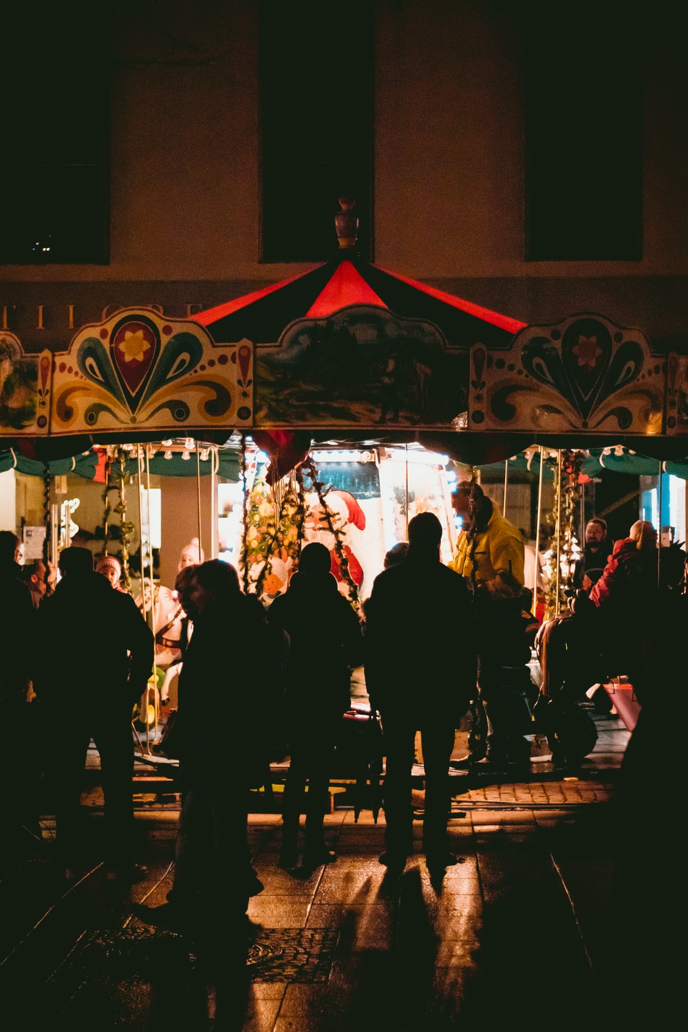 people riding and standing by merry-go-round at nighttime