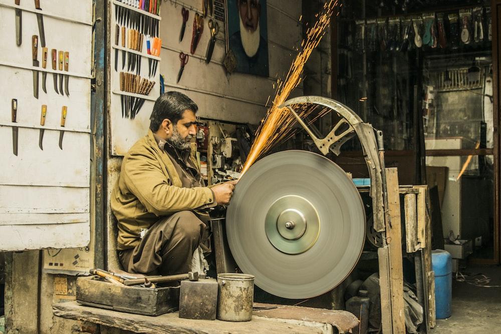 man sharpening tool on gray machine inside room