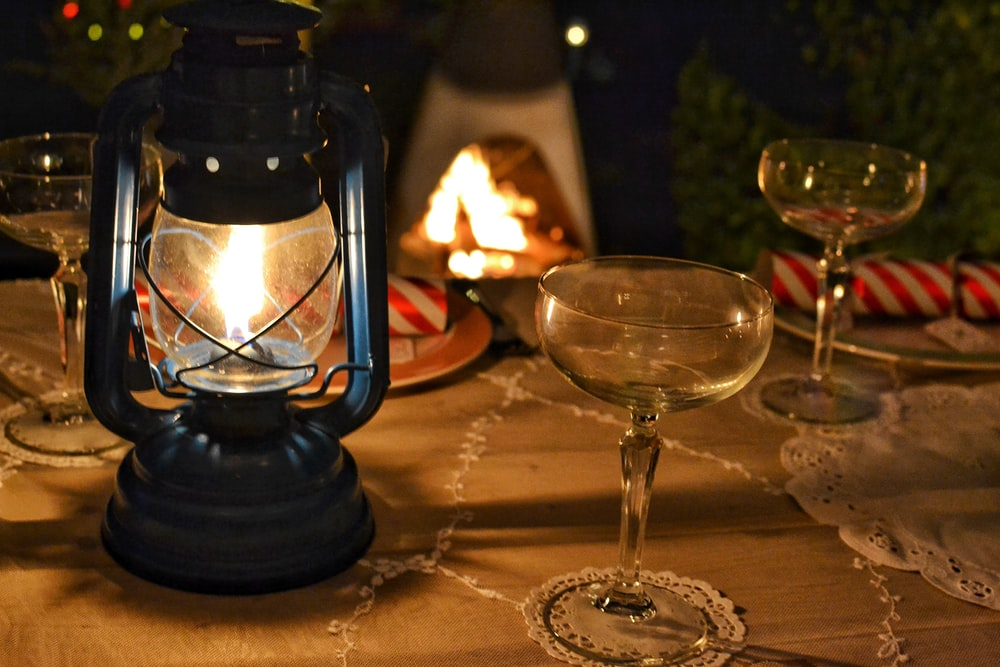 lighted tubular lantern beside empty cocktail glass