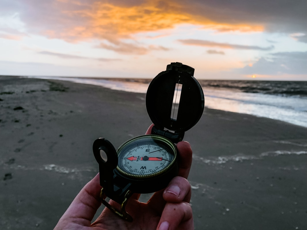 person holding black and white compass for outdoor navigation