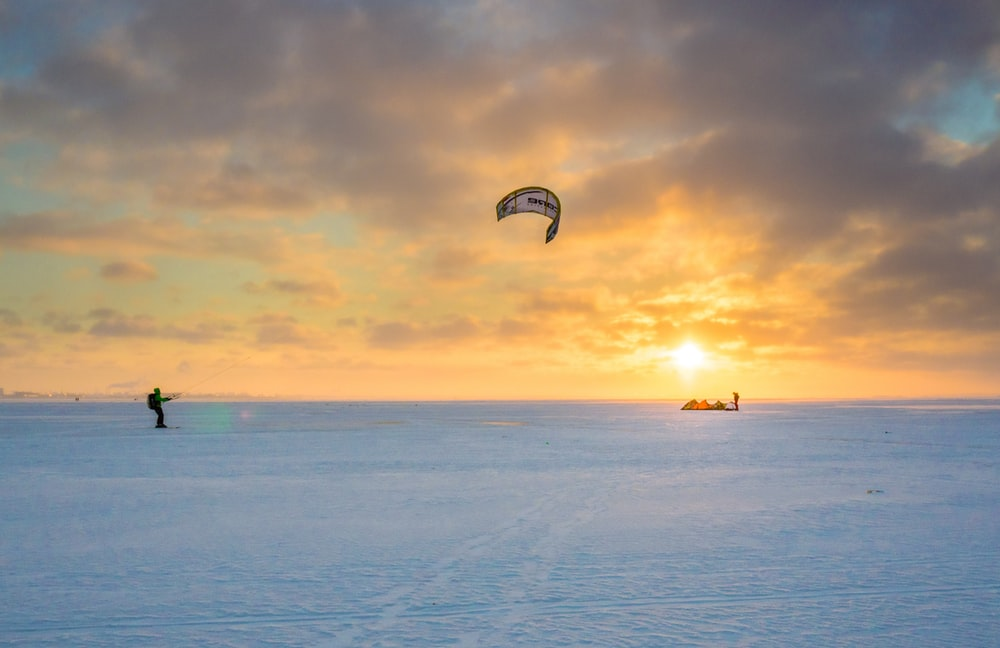 person parachute water skiing during golden hour