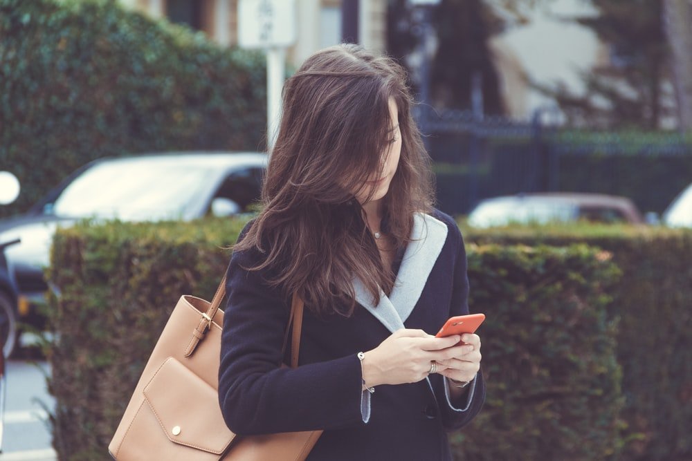 selective focus photography of woman standing near topiary while holding smartphone
