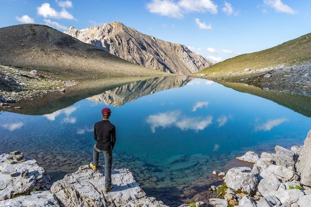 man standing on seacliff facing mountain range