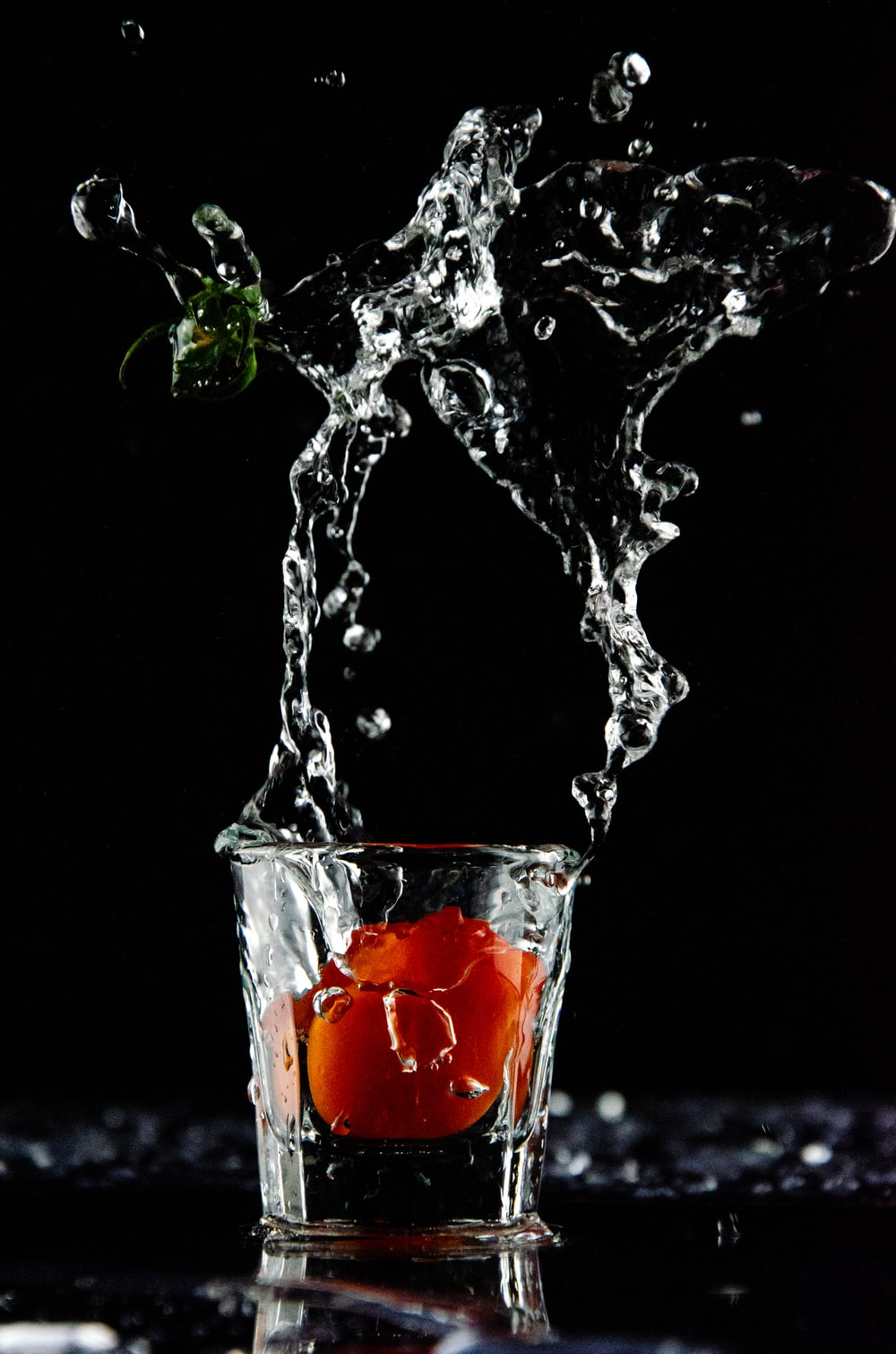 orange fruit dropped on shot glass with clear liquid spills