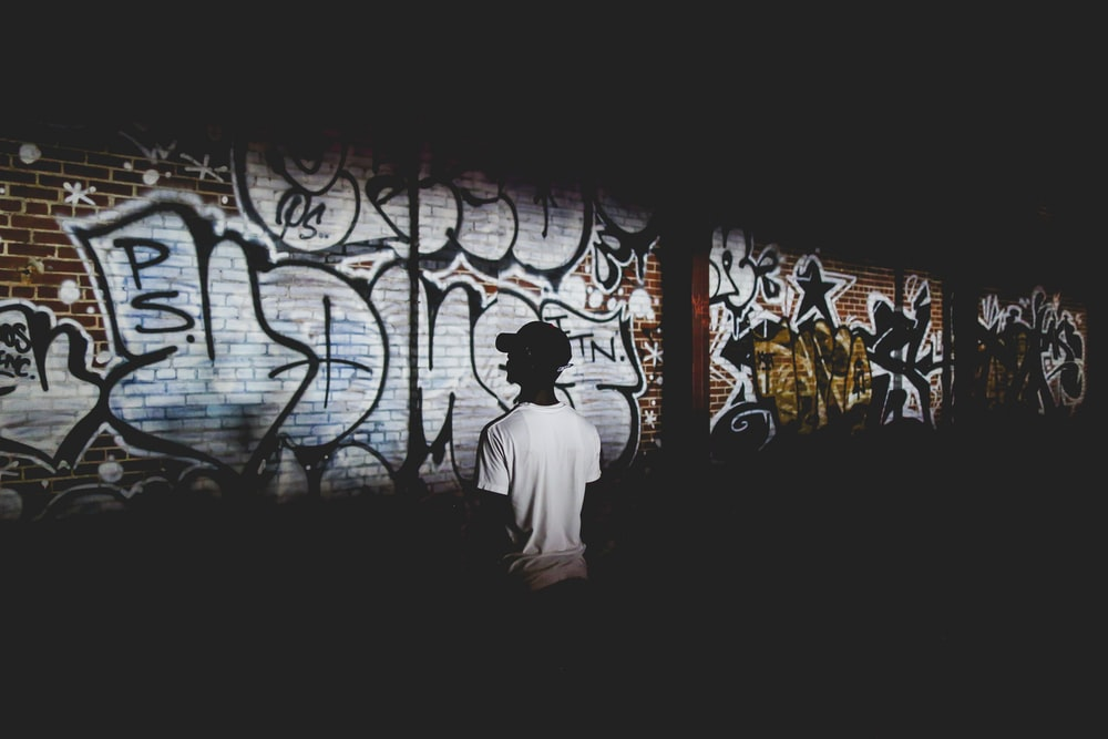man standing beside wall with graffiti text
