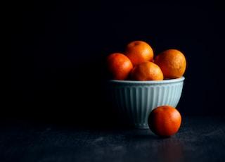 orange fruit in white ceramic bowl