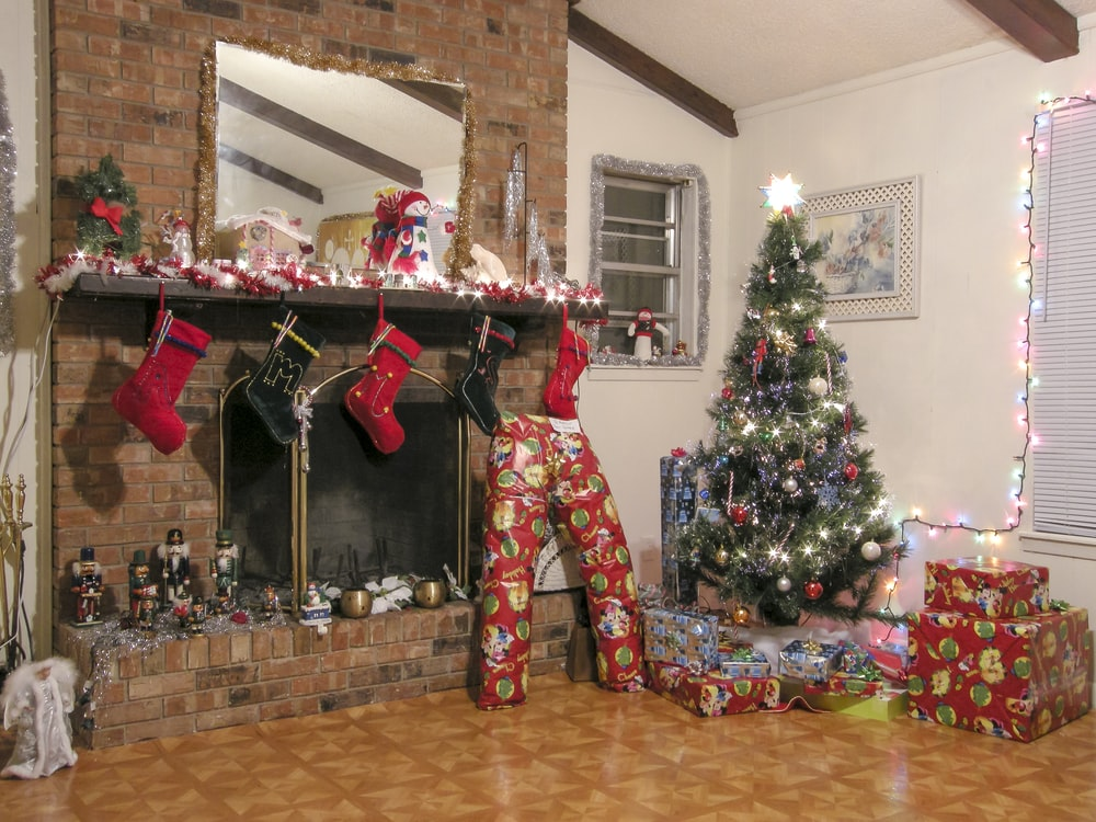 fireplace near Christmas tree and gift boxes