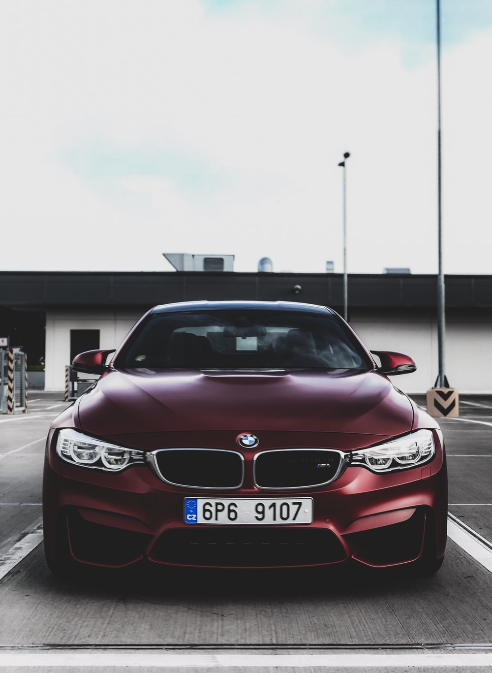red BMW car parked near building