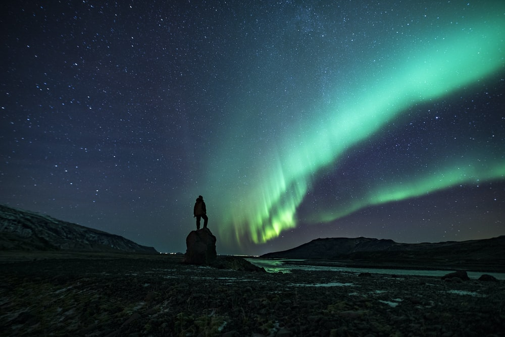 silhouette of person under Northern lights