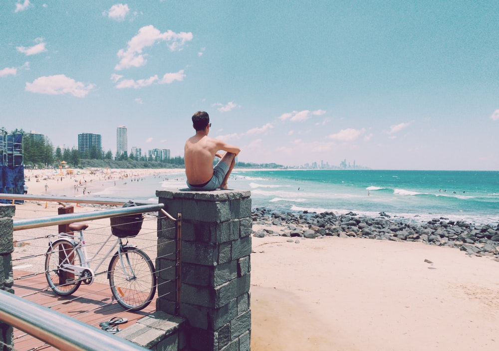 man sitting on the top of concrete post facing the beach