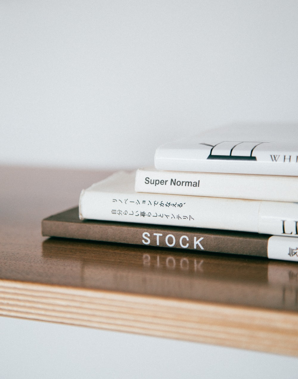 four assorted-title books on wooden panel