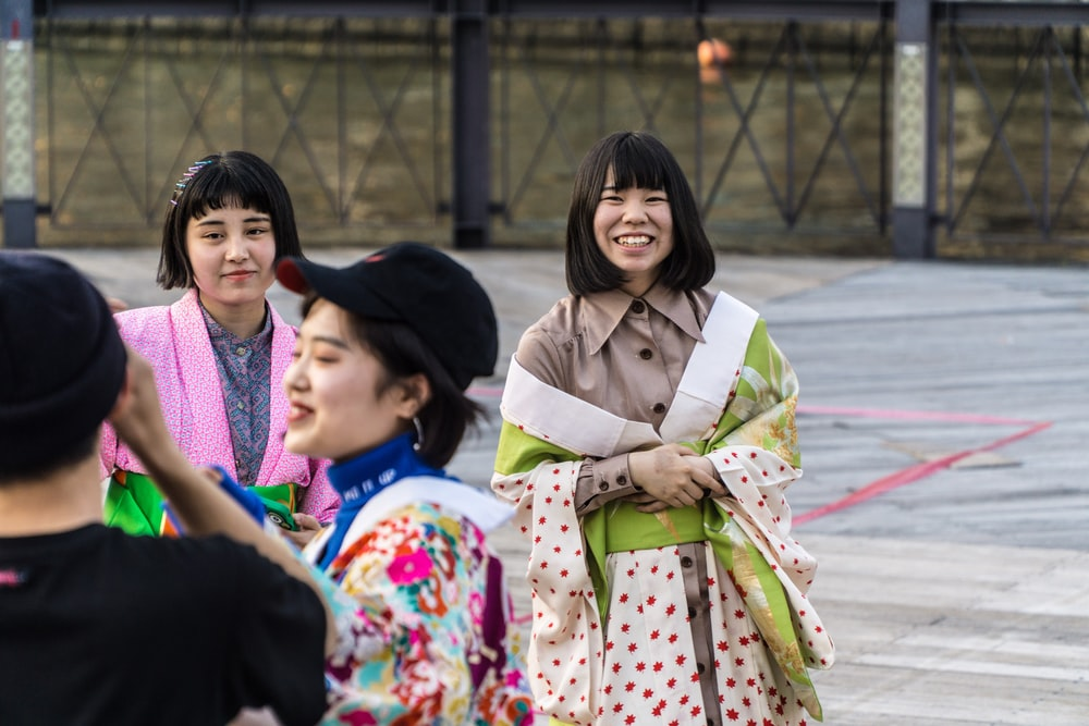 four smiling women standing on pavement during daytime