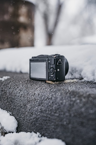 black point-and-shoot camera on gray surface outdoor