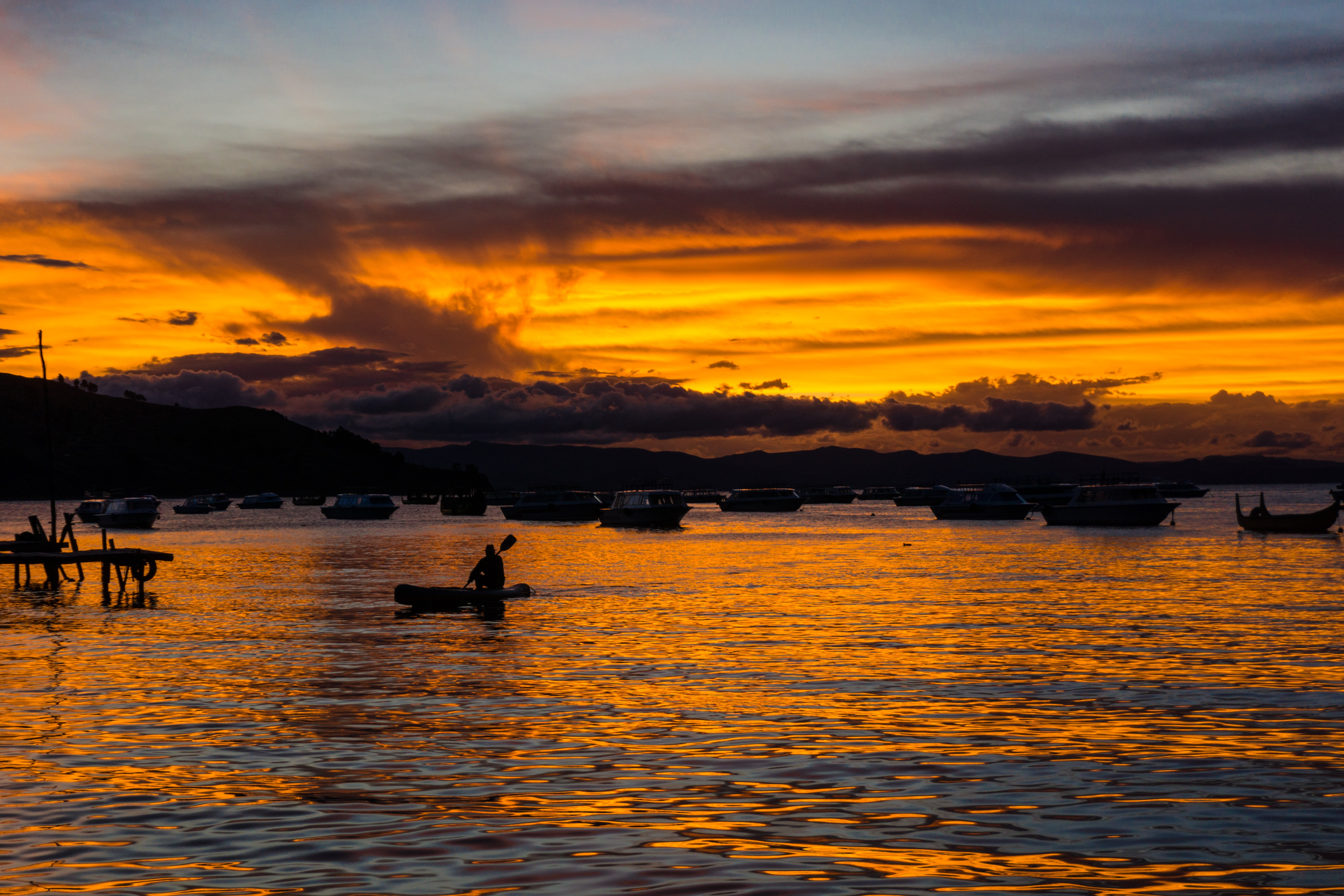 silhouette of person riding on boat during golden hour
