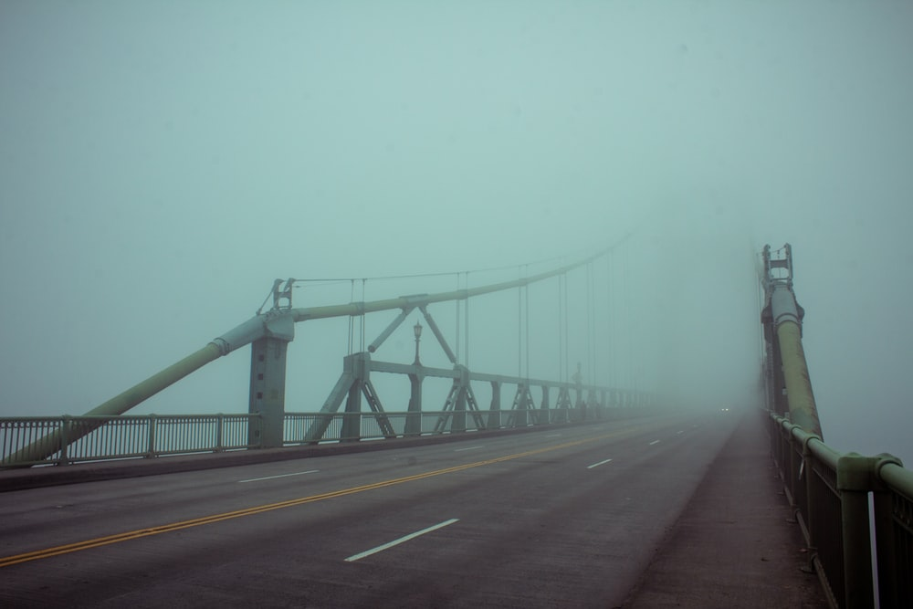 suspension bridge covered with fogs