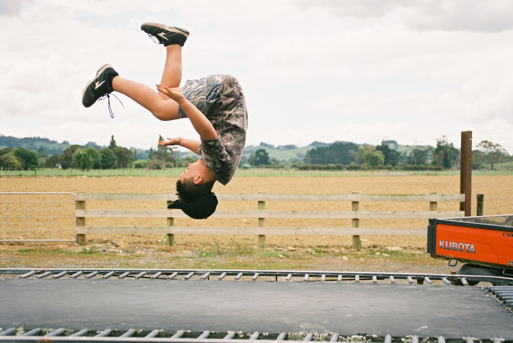 girl jumping in road during daytime
