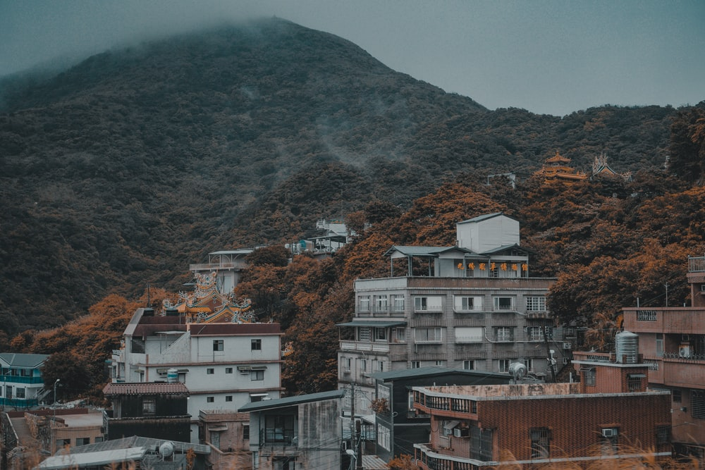 concrete buildings beside mountains at daytme