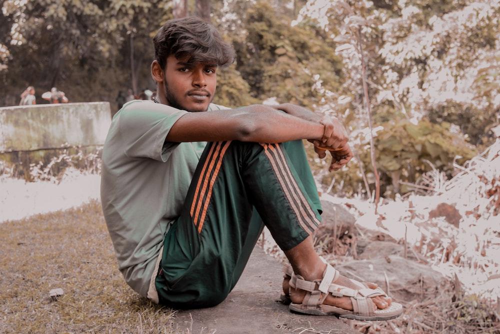 man sitting on ground during daytime
