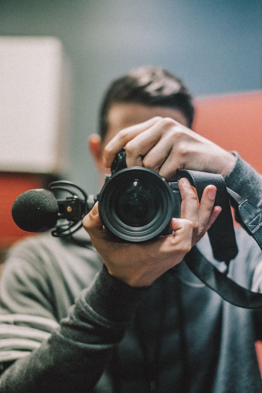 man holding DSLR camera at daytime