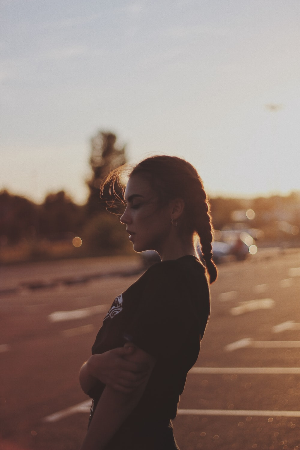 close-up photography of woman standing on parking lot
