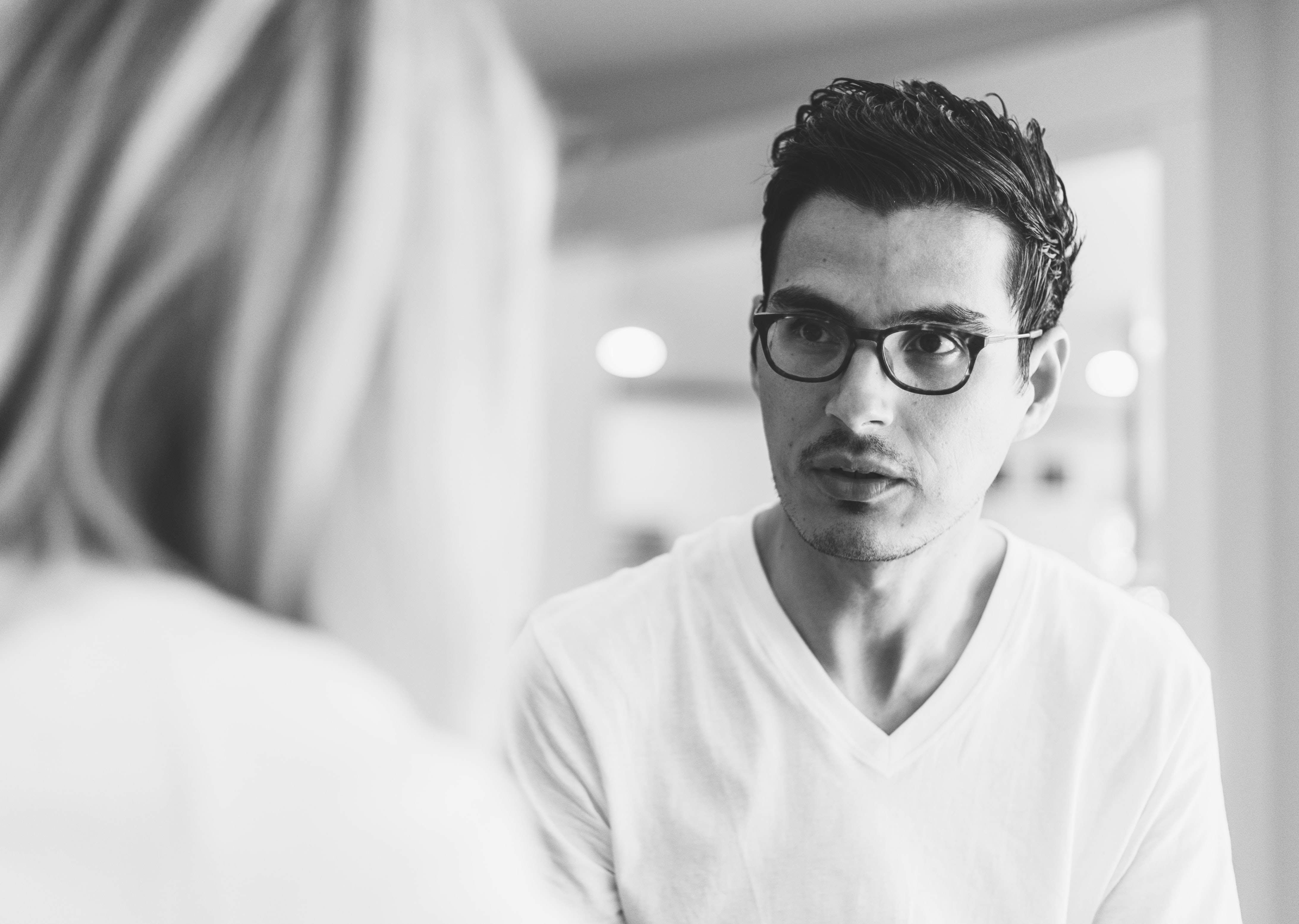 grayscale photography of man wearing eyeglasses in front of woman