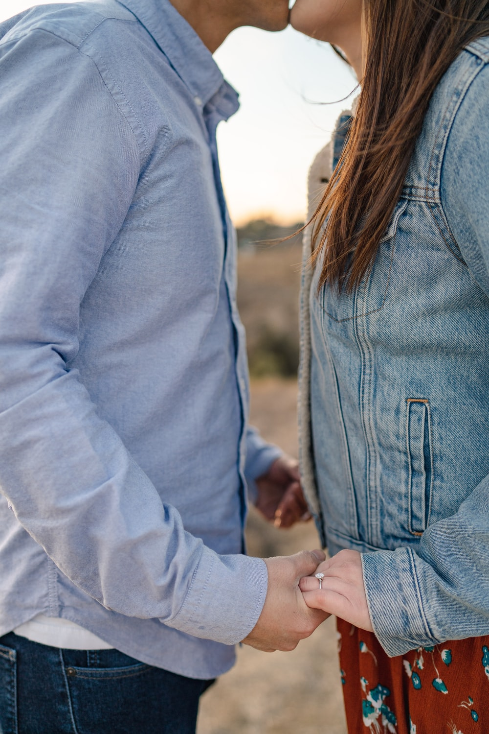 man and woman kissing while holding hands
