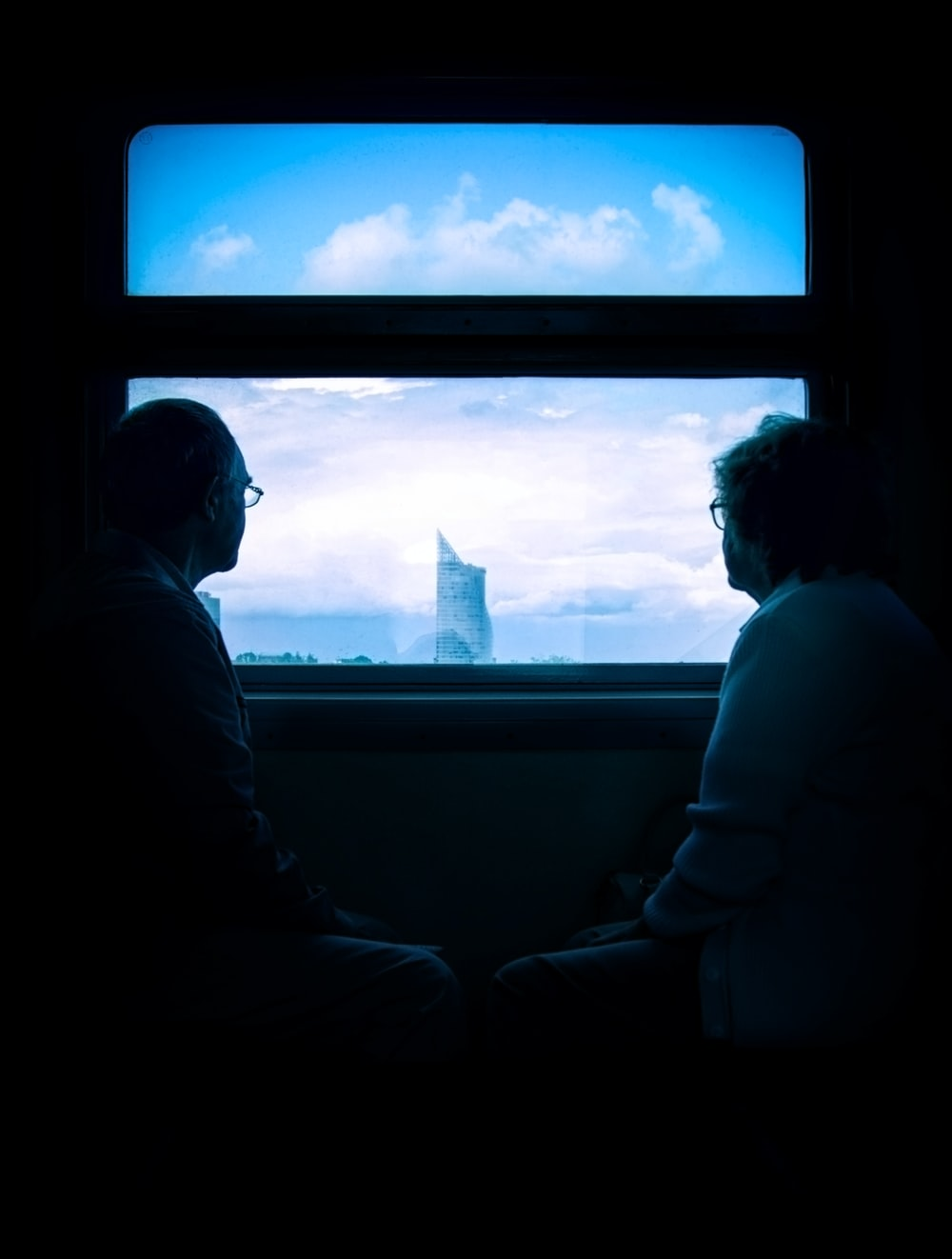 man and woman standing beside window
