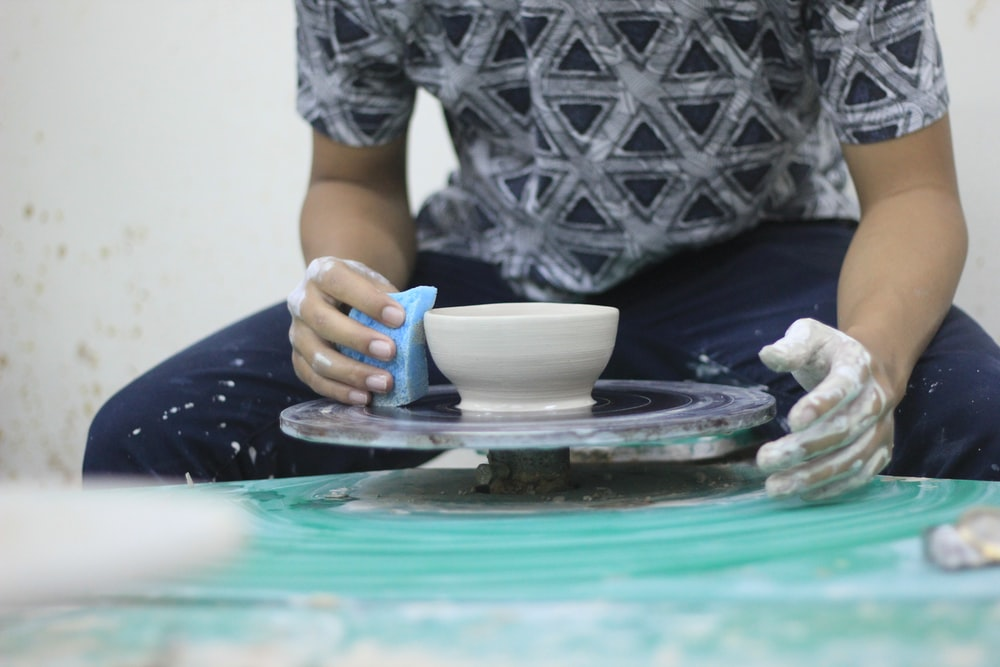 person making white pot