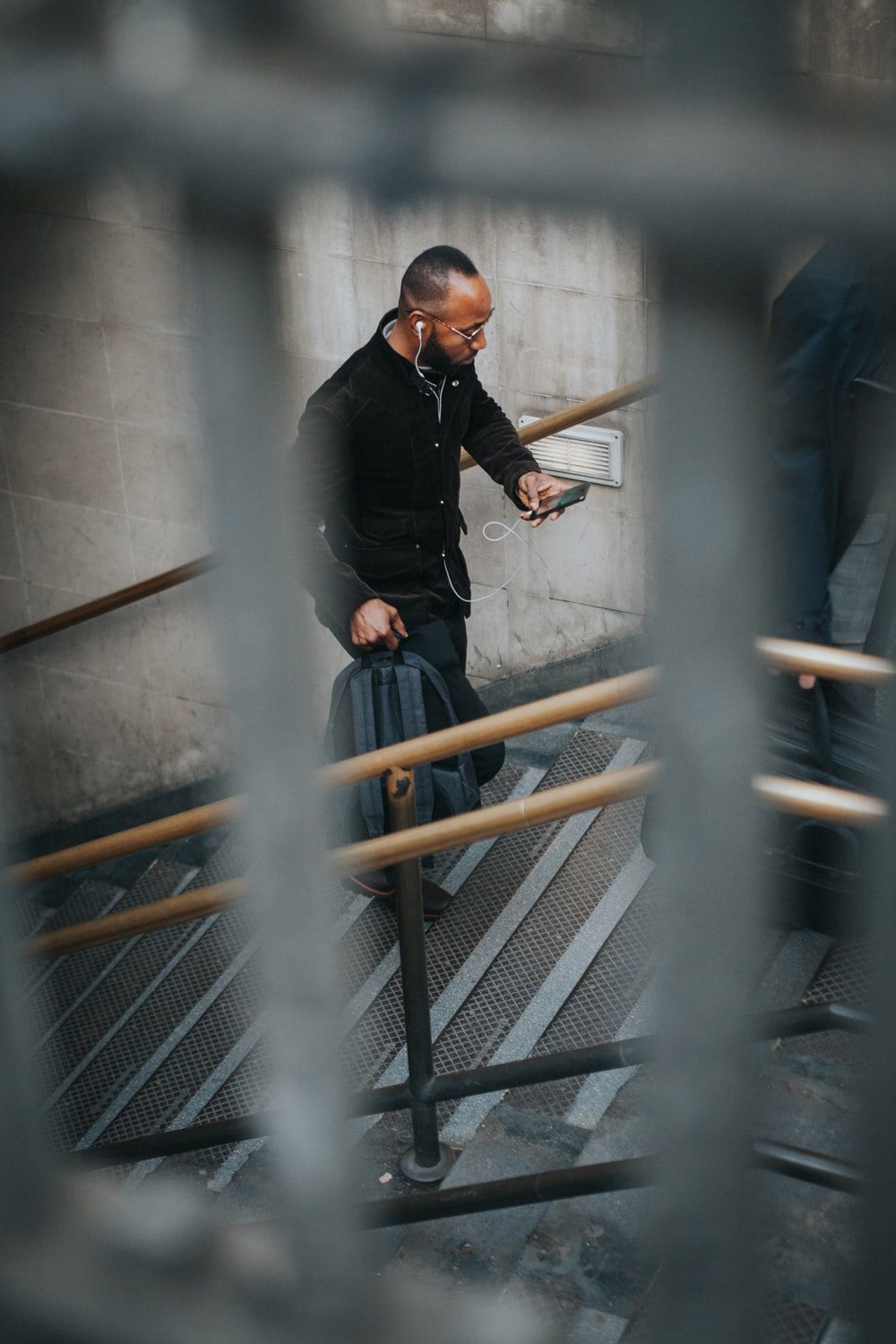 man on stairs while using smartphone and carrying backpack