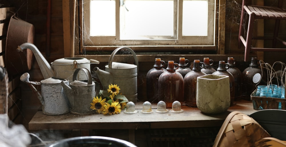 assorted-color jugs and watering cans