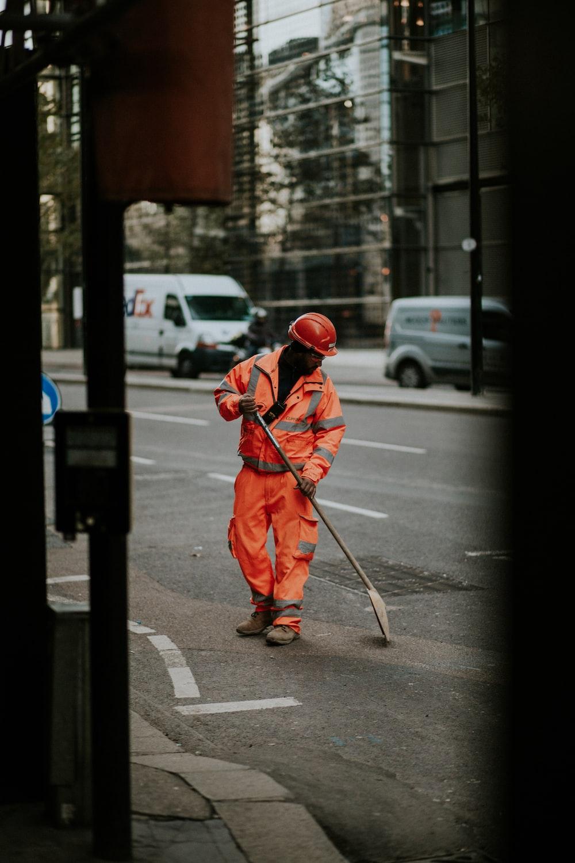 man wearing orange bunker gear on road