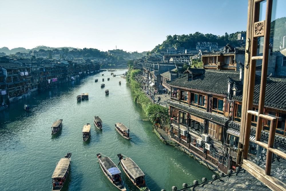 bird's eye view photography of boats river between houses