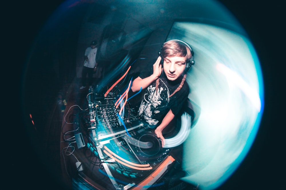 shallow focus photo of man using DJ turntable