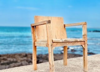 brown wooden chair near body of water