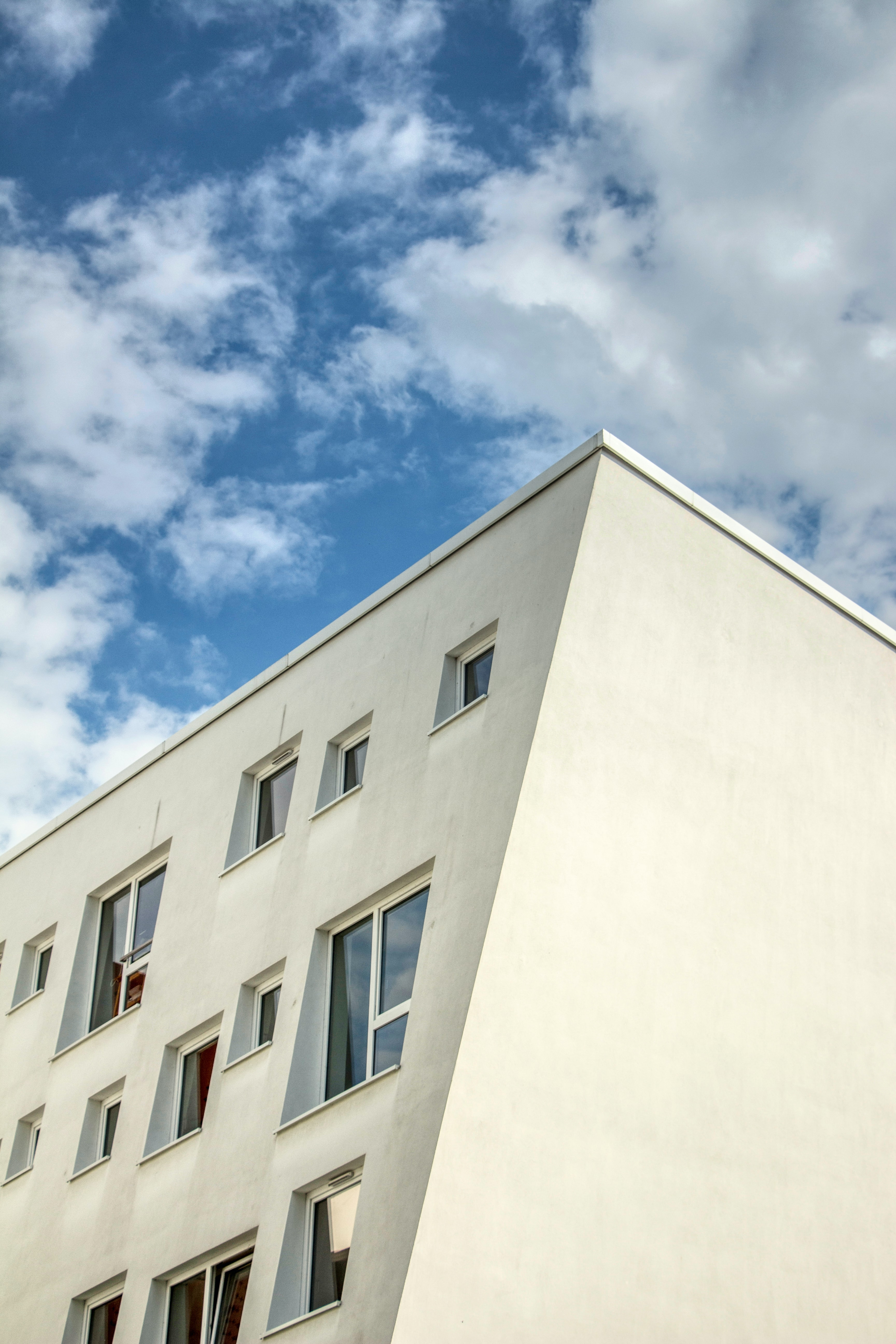 white concrete building under blue and white cloudy daytime sky