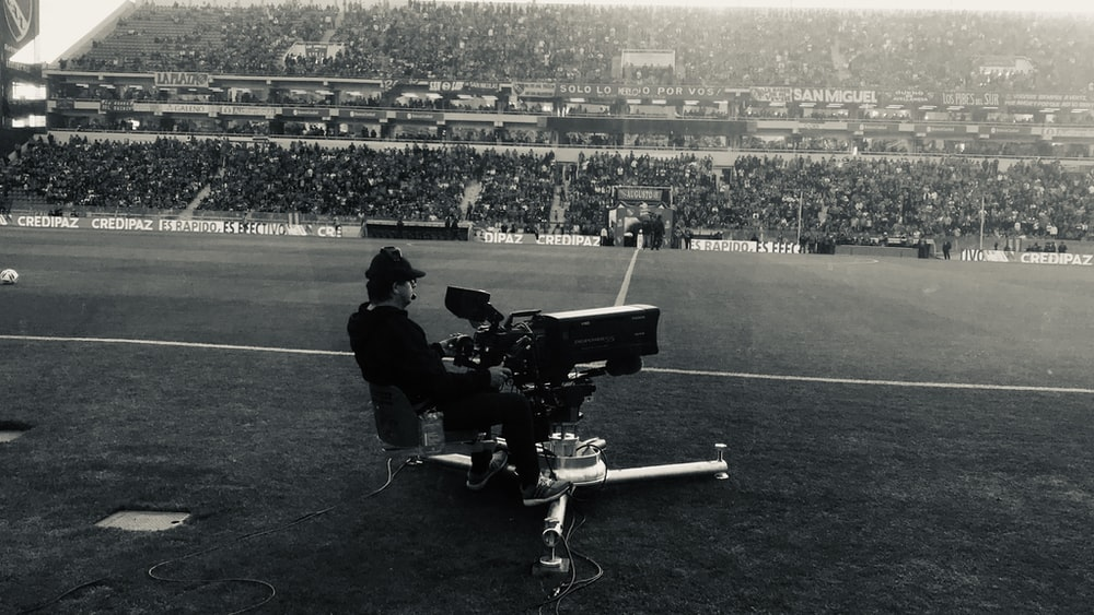 man sitting with camera on field
