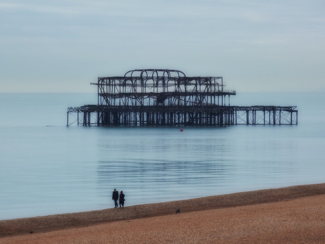 A calm quiet and windless Winter day along Brighton Seafront UK, a couple walk their dog along the pebble beach.  The scene looked so romantic I just had to photograph it.  The old rusty pier giving the scene atmosphere.